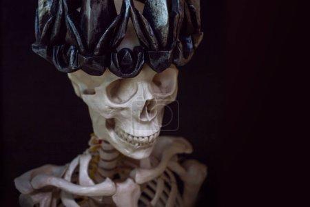 Photo pour Le crâne dans la couronne. Grim nécromancien en couronne gothique. Fond noir, concept Halloween, espace libre - image libre de droit
