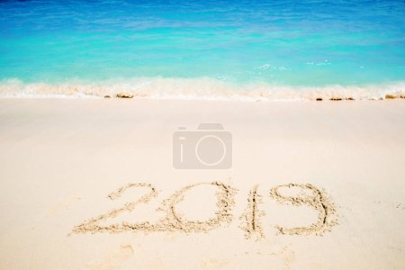 Inscription on the sand, celebrate the new year in the tropics. New year holidays