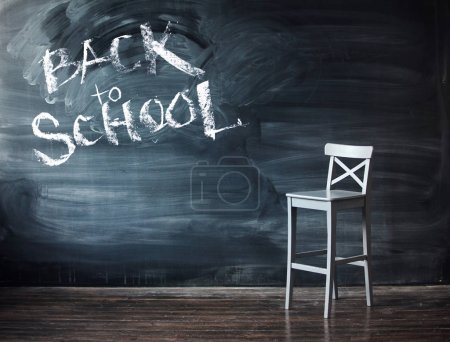 Sign back to school on a black chalkboard. Wooden chair against a school desk for the letter