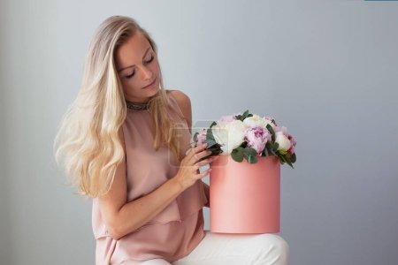 Photo pour Femme blonde heureuse avec des fleurs dans une boîte à chapeau. Bouquet de pivoines. Jeune fille vêtue d'une robe rose tendre avec une rose bouquet de pivoines - image libre de droit
