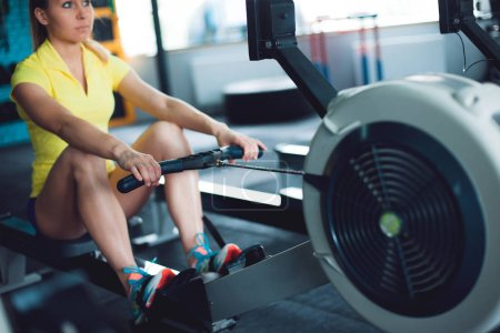 Rowing in the gym. Young woman training using rowing machine