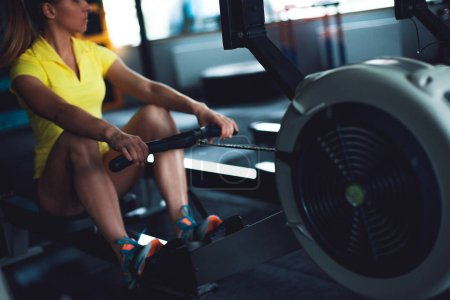 Photo for Rowing in the gym. Young woman training using a rowing machine - Royalty Free Image