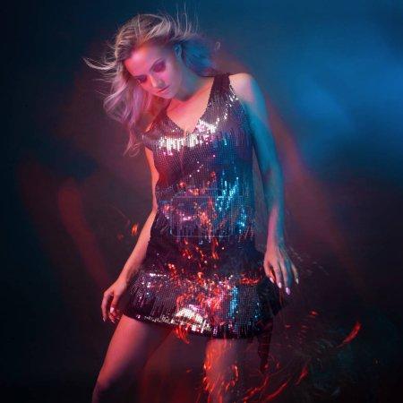 Photo pour Lumineuse et élégante jeune femme danse en club, lumière de couleur, effets de mouvement. Fond noir, longue exposition - image libre de droit