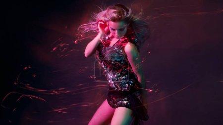 Photo pour Jeune femme lumineuse et élégante dansant en club, lumière de couleur, effets de mouvement. Fond noir, longue exposition - image libre de droit