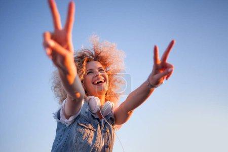Photo pour Jeune femme élégante avec des cheveux très luxuriants montrent signe de victoire. Jeune femme avec de gros écouteurs. portrait extérieur d'une fille à la mode - image libre de droit