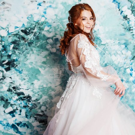 Photo for Pretty and romantic bride in wedding dress with long sleeves. Young redheaded woman in wedding dress, abstract blue background - Royalty Free Image