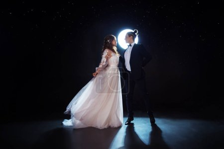 Mysterious and romantic meeting, the bride and groom under the starry sky. Hugs together. Man and woman, wedding dress.