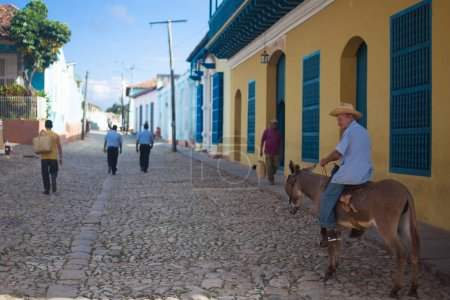 TRINIDAD, CUBA - NOVEMBER 9, 2012: Old man in the hat riding a donkey on the street