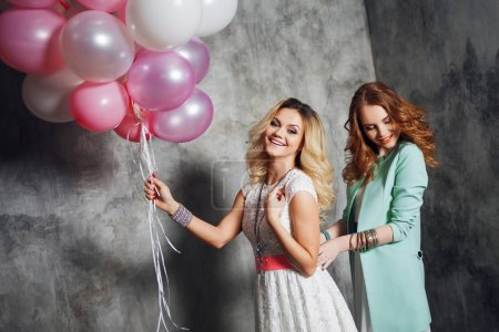 Blonde and redhead. Two young charming girlfriends at the party. Happy and cheerful girl with balloons.