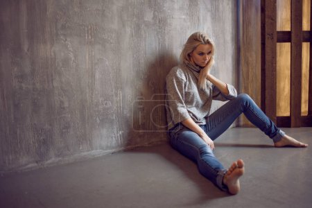 Photo for Depressed woman. blonde girl sitting on the floor, sadness and depression, concept of psychological problem - Royalty Free Image
