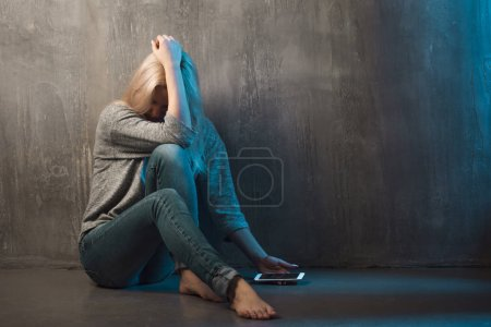 Helpline, psychological assistance. Suffering young woman sitting in a corner with a phone in her hand
