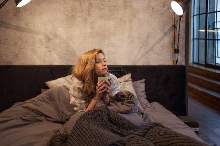 Photo pour Fille le matin boire du café au lit. Tôt le matin, le soleil ne s'était pas encore levé - image libre de droit