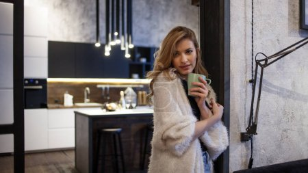 Photo for Portrait of a beautiful blonde in the interior of her apartment. Modern loft, beautiful and confident girl drinks morning coffee - Royalty Free Image