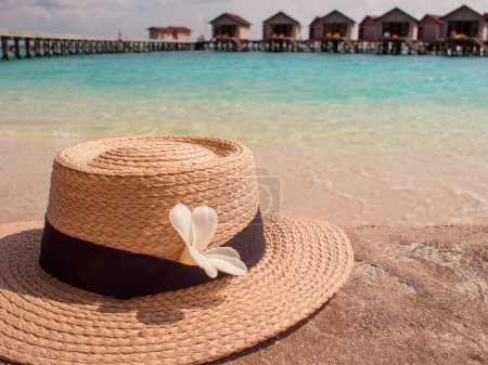 Photo for Still life with a hat and shades of palm leaves, a beach holiday on the Islands. Far away Bungalow in the water - Royalty Free Image