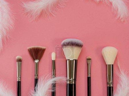 Photo pour Set de pinceaux de maquillage, outils de maquillage professionnels. Brosse douce et agréable pour maquillage, concept. Brosses et plumes blanches sur fond rose - image libre de droit