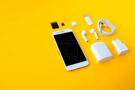Photo for Mobile kit with smartphone, headphones and chargers. Yellow background, Copy space to the left - Royalty Free Image