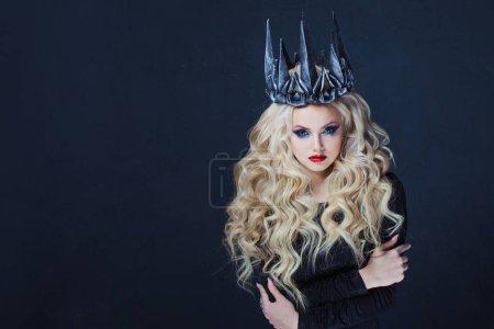 Photo pour Portrait d'une reine gothique. Belle jeune femme blonde dans la couronne en métal et le manteau noir. Image mystique - image libre de droit