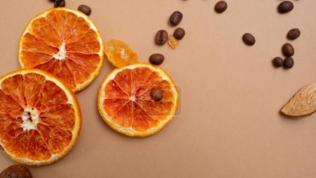 Photo for Citrus and spicy background with coffee beans and spices, warm ochre background. Copy space. Cinnamon and sugar crystals - Royalty Free Image