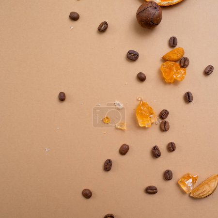 Photo for Citrus and spicy background with coffee beans and spices, warm ochre background. Copy space. Coffee, nuts and sugar crystals - Royalty Free Image