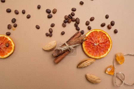 Photo for Citrus and spicy background with coffee beans and spices, warm ochre background. Copy space. Cinnamon, nuts and sugar crystals - Royalty Free Image