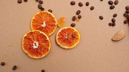 Photo for Citrus and spicy background with coffee beans and spices, warm ochre background. Copy space. Dried oranges, coffee and sugar crystals - Royalty Free Image