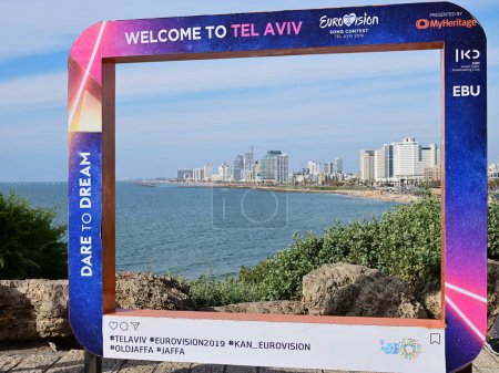 Photo pour Tel Aviv, Israel - March 5, 2019: Poster on the Jaffa Promenade with official Eurovision symbols Eurovision Song Contest 2019. Tel Aviv skyline and Mediterranean sea on background. Welcome to Tel Aviv - image libre de droit