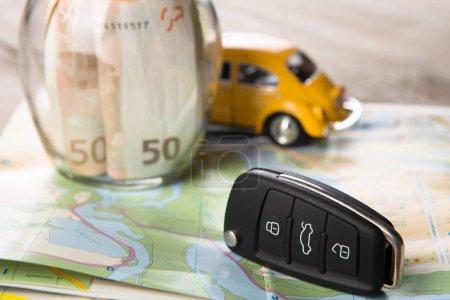 Photo pour Concept de location de voiture - clé de voiture et argent sur la carte routière - image libre de droit