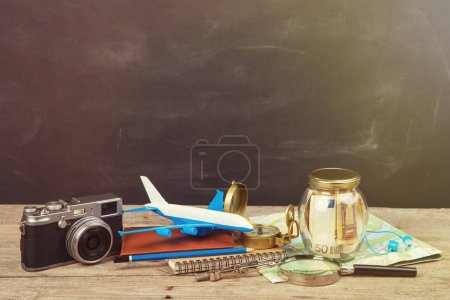 Photo for Jar with money for a travel, airplane, maps, passport, and other stuff for adventure on the blackboard background - Royalty Free Image