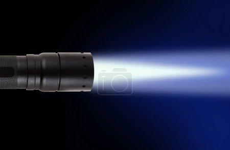 Photo pour Lampe de poche LED avec faisceau sur fond sombre - image libre de droit