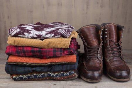 Photo pour Pile de pulls d'hiver tricotés sur fond en bois - image libre de droit