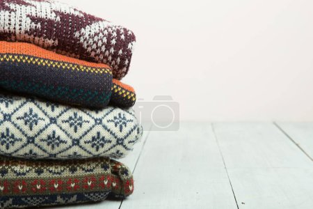 Photo for Pile of knitted winter sweaters on wooden background - Royalty Free Image