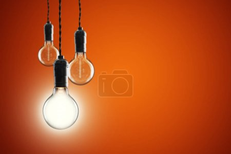 Photo for Idea and leadership concept Vintage incandescent Edison type bulbs on color wall - Royalty Free Image