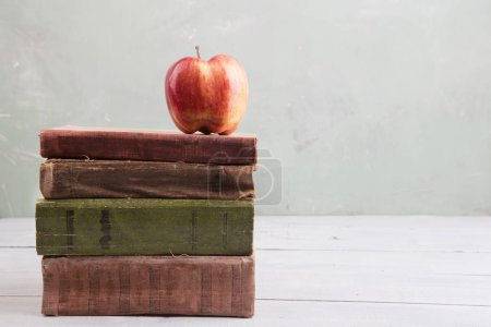 Photo for Apple on a stack of books on the table - Royalty Free Image