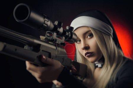 Girl on a black background in a nun dress posing w...