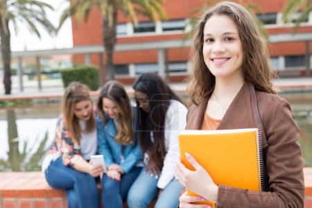 Smiling student posing with books in university campus