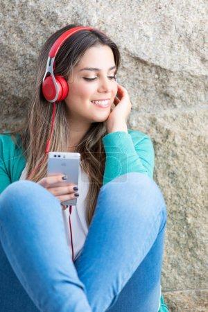 Photo pour Belle jeune femme vous détendre sur le canapé tout en écoutant de la musique - image libre de droit