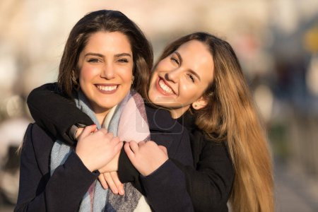 Photo for Young pretty girls best friends smiling and having fun, walking at the city. Shopping. Wearing stylish outerwear. Bright make up. Positive emotions. Outdoors lifestyle fashion close up portrait - Royalty Free Image