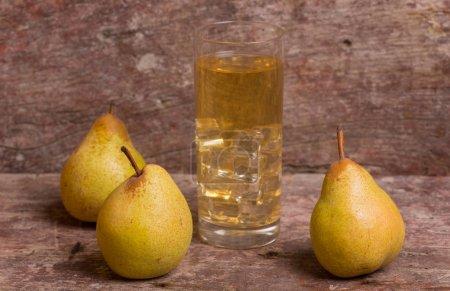 Photo pour Poire et un verre de jus sur une table en bois, photo de studio - image libre de droit