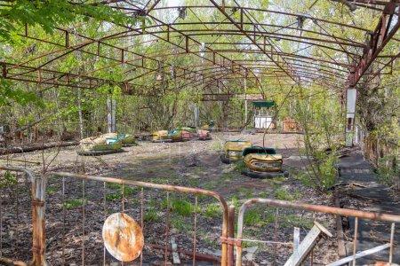 Photo pour Vieux métal rouillé cassé voitures électriques radioactives pour enfants abandonnés, le parc de la culture et des loisirs dans la ville de Pripyat, la catastrophe de Tchernobyl, Ukraine . - image libre de droit