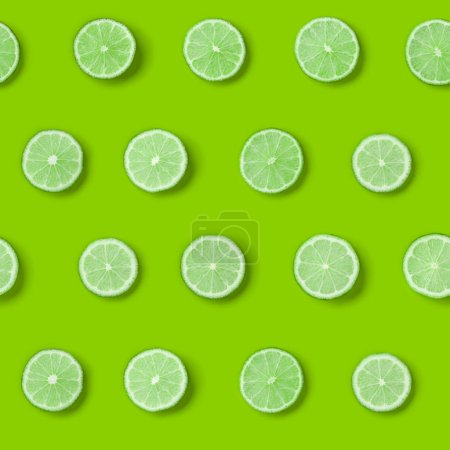 Photo for Fruit pattern of lime slices on green background. Flat lay, top view. - Royalty Free Image