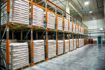 Hangar warehouse with rows of shelves with white p...