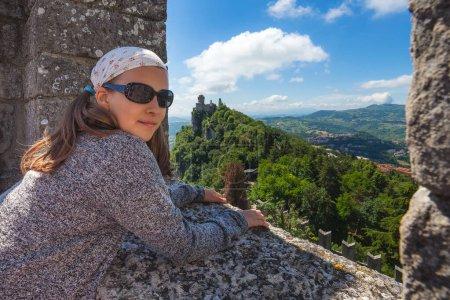 Photo pour Jeune fille touristique visitant les sites touristiques de Saint-Marin. Cesta ou Deuxième tour en arrière-plan - image libre de droit