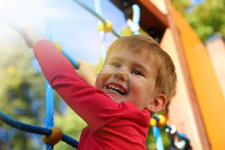 Little caucasian boy hanging on  the monkey bar by his hand to exercise at outdoor playgroun