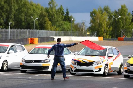 Photo for Starter man gives the go-ahead red flag to start car racing - Royalty Free Image
