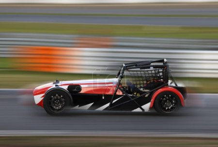 Photo for Race car racing at high speed on speed track with motion blur - Royalty Free Image