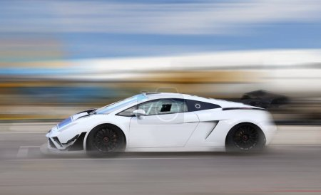 Photo for White race car racing at high speed on race track with motion blur - Royalty Free Image