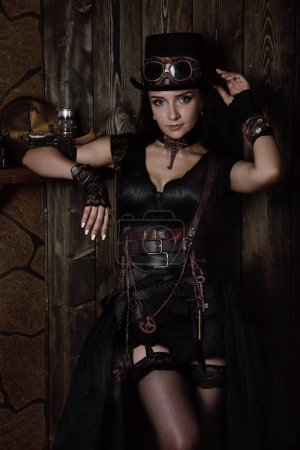 Photo for Beautiful sexy woman in the style of a steampunk over wooden vintage backgroun - Royalty Free Image