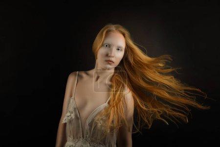 Photo pour Portrait d'art conceptuel mystique d'une jeune fille aux cheveux roux volant sur un backgroun noir - image libre de droit