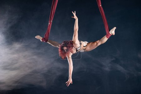 Photo for Female athletic, sexy and flexible aerial circus artist with redhead dancing in the air on the silk. - Royalty Free Image