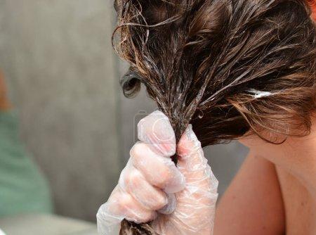 Photo pour Une jeune femme se teint les cheveux à la maison. La fille qui colore ses cheveux dans sa propre salle de bain. Quarantaine, soins capillaires à domicile, concept de séjour à la maison . - image libre de droit